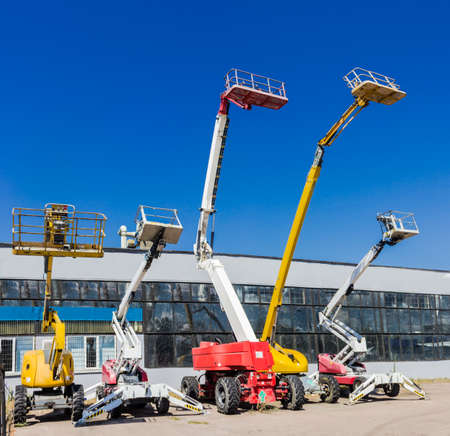 Photo for Several various mobile aerial work platform - self propelled hydraulic articulated boom lift against the sky and industrial building - Royalty Free Image