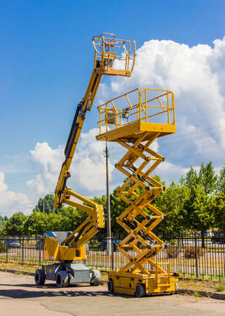 Photo for Two types of mobile aerial work platform - yellow scissor hydraulic lift and yellow hydraulic articulated boom lift against the sky with clouds and trees - Royalty Free Image