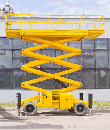 Foto de Yellow scissor wheeled lift on an asphalt ground on the background of the industrial building - Imagen libre de derechos
