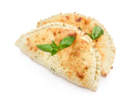 Foto de Two baked calzone - closed type of pizza that is folded in half decorated with basil twigs on a white background  - Imagen libre de derechos