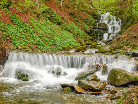 Photo for Multi-level water cascade of waterfall Shypit in beech forest in the Carpathian mountains near the village Pylypets in early spring, Ukraine - Royalty Free Image