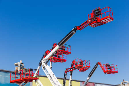 Foto de Fragment of the booms with baskets and top parts of different articulated boom lifts and scissor lifts on a background of clear sky - Imagen libre de derechos