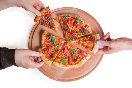 Foto de Pizza with sausage and thick outer rings made with cheese-filled dough. Hands taking pizza wedges from the wooden serving board ,  top view on a white background  - Imagen libre de derechos