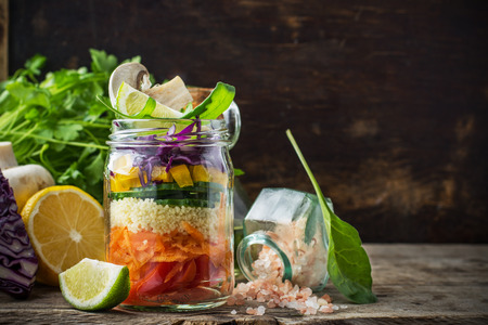 Photo pour Bright rainbow salad layers of tomatoes, carrots, couscous, yellow pepper, red cabbage, arugula and mushrooms with butter and sea salt on a pink background vegetables and herbs. Trends in healthy eating. Selective focus. - image libre de droit