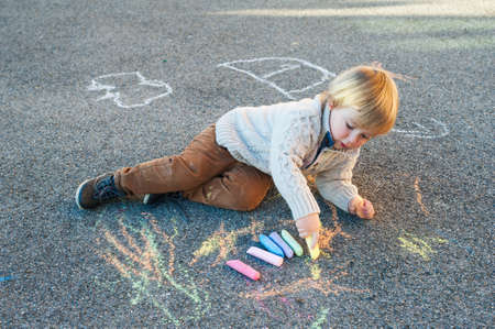 Photo for Cute toddler boy drawing with chalk on a nice day outdoors - Royalty Free Image
