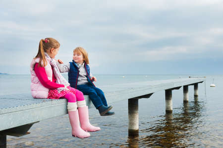 Cute kids playing by the lake resting on a pier