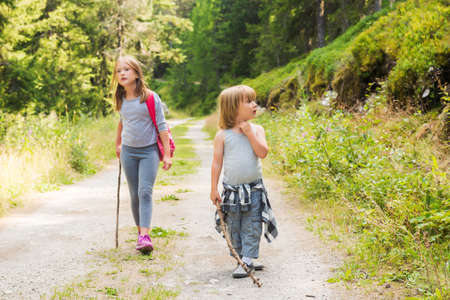 Two cute kids hiking in forest