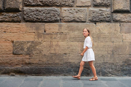 Photo for Little girl walking down the street, wearing white summer dress - Royalty Free Image