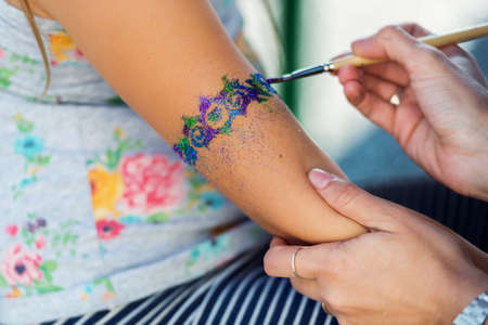 Photo pour Little girl getting glitter tattoo at birthday party - image libre de droit