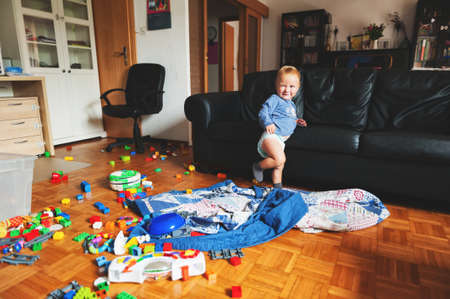 Photo pour Adorable 1 year old baby boy with funny facial expression playing in a very messy living room - image libre de droit