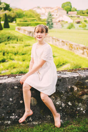 Photo for Pretty little girl playing in a beautiful garden on a nice summer day, wearing vintage style white dress - Royalty Free Image
