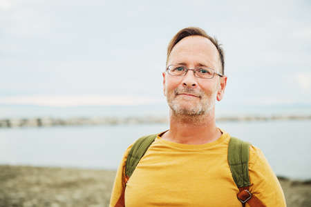 Foto de Handsome man on summer vacation by the sea, wearing yellow safran t-shirt and backpack - Imagen libre de derechos