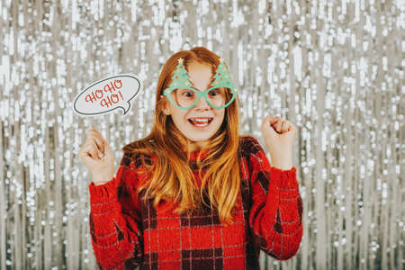 Photo for Christmas portrait of cute little girl against silver background, wearing red pullover, holding festive party props for photo booth - Royalty Free Image