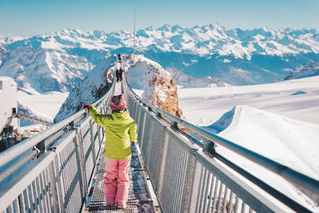 Photo for Kid girl playing with snow on the top of the mountain, winter vacation with children, family activities in Alps. Back view. Image taken in Glacier 3000, canton of Vaud, Switzerland - Royalty Free Image