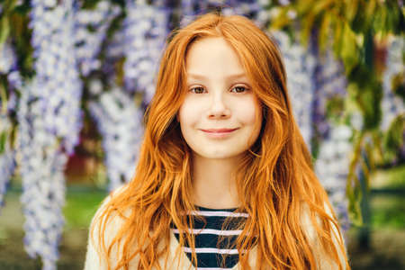 Foto de Close up portrait of adorable 9-10 year old red-haired kid girl posing in wisteria - Imagen libre de derechos