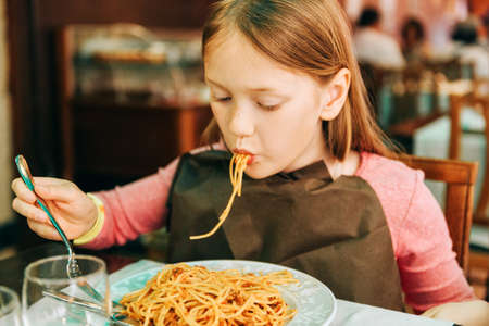 Photo pour Adorable little girl eating spaghetti with bolognese sauce in the restaurant - image libre de droit