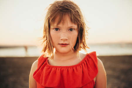 Foto de Close up portrait of sweet little girl with short bob haircut resting by the sea at sunset - Imagen libre de derechos