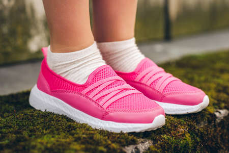 Photo pour Close up image of pink modern sneakers wearing by a girl - image libre de droit