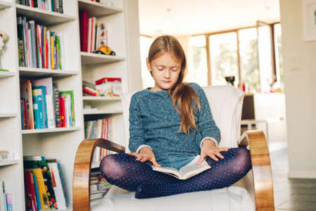 Photo pour Cute little girl sitting in a white chair at home and reading a book - image libre de droit