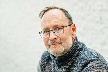 Photo pour Outdoor portrait of 50 year old man wearing brown pullover and eyeglasses - image libre de droit