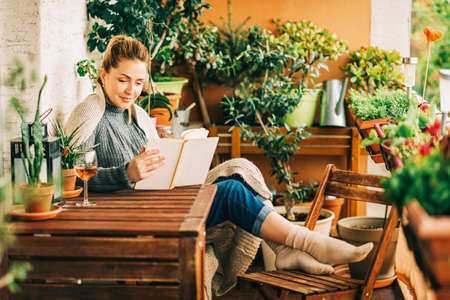 Photo pour Young beautiful woman relaxing on cozy balcony, reading a book, wearing warm knitted pullover, glass of wine on wooden table - image libre de droit