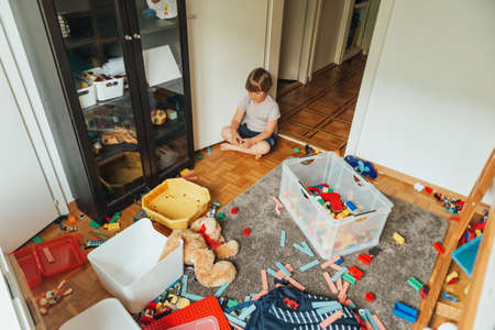 Photo pour Indoor portrait of a child playing in a very messy room, throwing teddy bear on the floor - image libre de droit