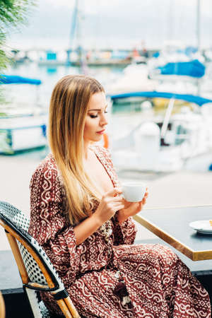 Photo for Outdoor portrait of beautiful woman resting in cafe with cup of coffee - Royalty Free Image