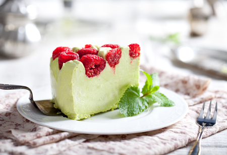 Photo pour Pistachio mousse cake, cheesecake with fresh raspberry on white plate with mint leaves - image libre de droit