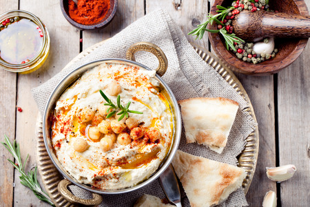 Photo for Hummus, chickpea dip, with rosemary, smoked paprika and olive oil in a metal bowl with pita - Royalty Free Image