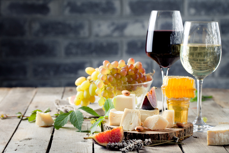 Photo pour Grape, cheese, figs and honey with a glasses of red and white wine on a stone and wood background - image libre de droit