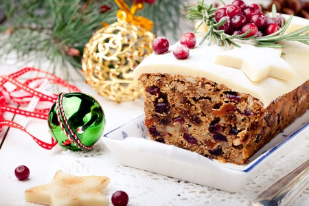 Foto de Traditional Christmas Fruit Cake pudding with marzipan and cranberry and rosemary decor on a Christmas decoration background - Imagen libre de derechos