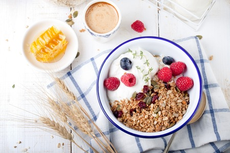 Photo for Granola with pumpkin seeds, honey, yogurt and fresh berries in a ceramic bowl on white background. - Royalty Free Image