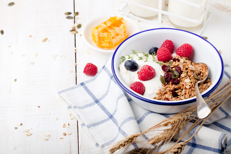 Photo pour Granola with pumpkin seeds, honey, yogurt and fresh berries in a ceramic bowl on white background. - image libre de droit