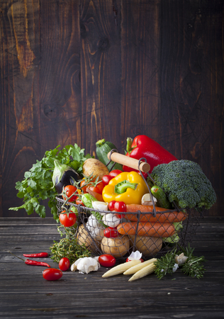 Photo pour Vegetables variety in a wire basket on a wooden background - image libre de droit