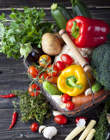 Photo pour Vegetables variety in a wire basket on a wooden background. - image libre de droit