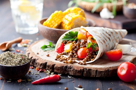 Photo pour Vegan tortilla wrap, roll with grilled vegetabes and lentil and boiled corn cob on a wooden background - image libre de droit