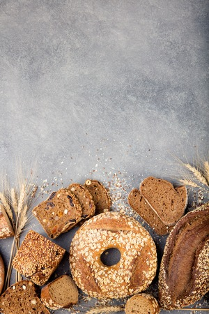 Foto de Assortment of baked bread on stone table background Composition with bread slices and rolls Copy space - Imagen libre de derechos