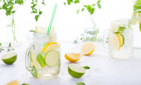 Photo for Lemonade with ice, lemon and lime slices in a jar with straw in a white summer wooden background - Royalty Free Image