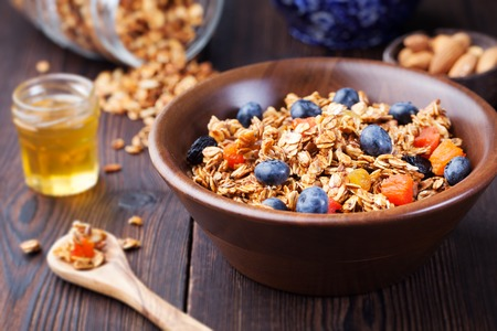 Photo for Healthy breakfast. Fresh granola, muesli with berries, honey and milk in a wooden bowl on a wooden background Top view - Royalty Free Image