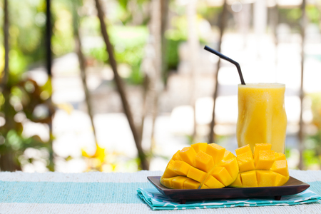 Foto de Fresh tropical fruit smoothie mango juice and fresh mango on a outdoor tropical background Copy space - Imagen libre de derechos