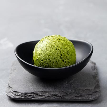 Foto de Green tea matcha ice cream scoop in bowl on a grey stone background - Imagen libre de derechos