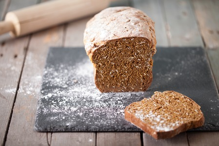 Photo for Fresh Irish soda bread with oat sliced on a slate cutting board Wooden background Copy space Selective focus - Royalty Free Image