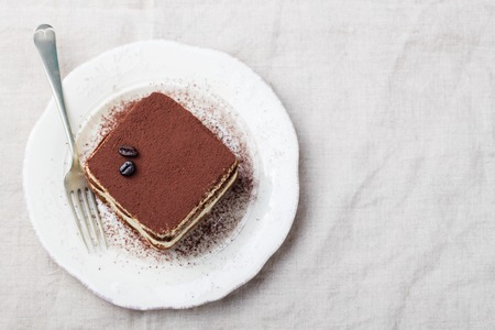 Photo for Tiramisu, traditional Italian dessert on a white plate Top view Copy space - Royalty Free Image