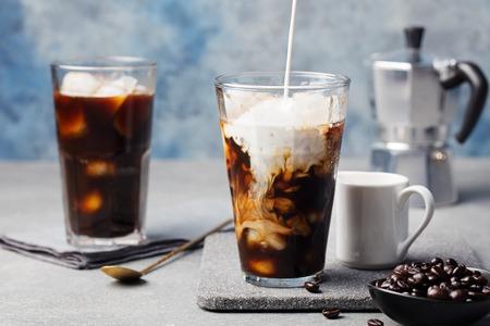 Photo for Ice coffee in a tall glass with cream poured over and coffee beans on a grey stone background - Royalty Free Image