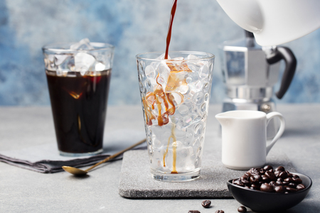 Foto de Ice coffee in a tall glass and coffee beans on a grey stone background. - Imagen libre de derechos