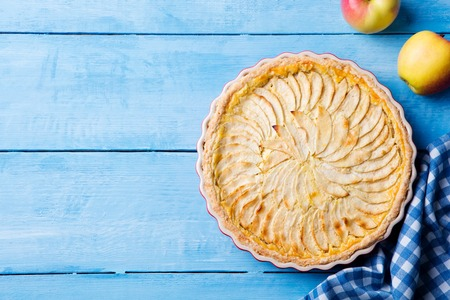 Photo for Apple pie with cream on a blue wooden background. Top view. Copy space - Royalty Free Image