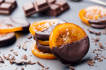 Photo for Candied orange slices in chocolate. Slate background. - Royalty Free Image