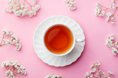 Foto de Cup of tea with fresh flowers on pink background. Top view. Copy space. - Imagen libre de derechos