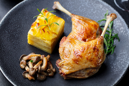 Photo for Duck legs confit with potato gratin and mushroom sauce . Restaurant serving - Royalty Free Image
