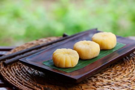 Foto de Mochi japanese dessert with mango on wooden plate Outdoor garden background - Imagen libre de derechos